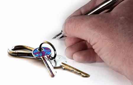 Schlüssel zu den Geschäftsräumen auf dem Tisch, Hand mit Stift zur Unterschrift