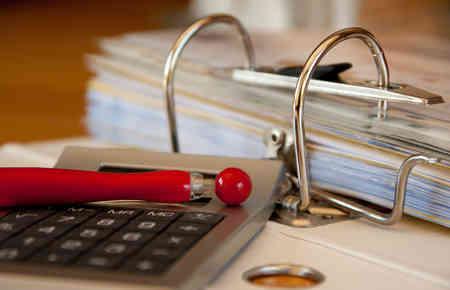 Aufgeschlagene Ordner mit Taschenrechner und Kugelschreiber, hier: welche Betriebsausgaben und kosten dürfen von der Corona Soforthilfe bezahlt werden